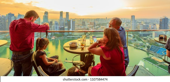 Singapore - May 3, 2018: family takes aperitif enjoying sunset and taking pictures from rooftop SkyBar CE LA VI of Marina Bay Sands hotel and casino. Financial district skyline on background.