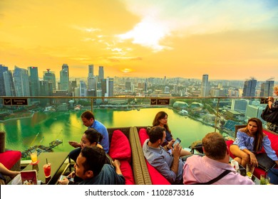 Singapore - May 3, 2018: lifestyle people enjoy sunset and panoramic views from rooftop SkyBar CE THE VI on 57th floor of Marina Bay Sands hotel and casino. Financial district skyline on background.