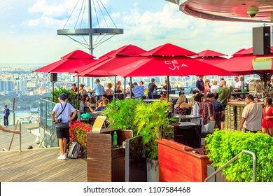 Singapore - May 3, 2018: Skypark Observation Deck at Marina Bay Sands Hotel overlooking architecture of SkyBar CE LA VI on 57th floor of Marina Bay Sands. Lifestyle people enjoy sunset and panorama.