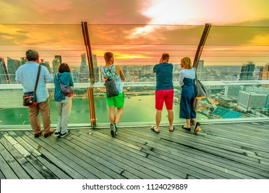 Singapore - May 3, 2018: tourists looking panoramic views from Observation Deck Skypark of Marina Bay Sands hotel and casino. Financial district skyline on background. Sunset shot.