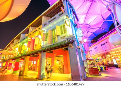 Singapore - May 5, 2018: street view and colorful futuristic umbrellas ceiling of Clarke Quay, an historical riverside quay with trendy restaurants and bars and colored houses. Night scene.