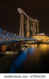SINGAPORE - May 5: Marina Bay Sands standing behind the Helix bridge late night on 5 May, 2016 in Singapore