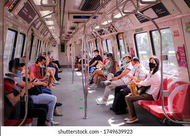 Singapore May2020 COVID-19 MRT train. Passengers wearing masks on public transport. Train uncrowded during coronavirus outbreak. Social distancing observed; stickers and markings on floor.