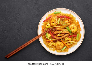Singapore Mei Fun in white plate on dark slate background. Singapore Noodles is chinese cuisine dish with rice noodles, prawns, char siu pork, carrot, red onion, napa cabbage. Chinese food. Copy space
