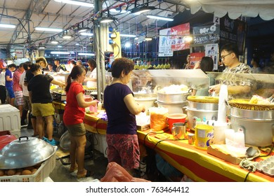 SINGAPORE- NOV 06, 2017: People buy foods in the night market in Singapore.  Singapore's night markets have much to offer the discerning traveler
