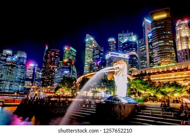 SINGAPORE - NOV 22, 2018: View of the business district and the The Merlion Park at a landmark name Marina bay with a lot of skyscrapers in the background and trial lights from moving objects at night