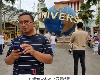 SINGAPORE- Nov 7, 2017: Visitors taking photos in front of large rotating globe fountain, famous picturesque of Universal Studios Singapore, a theme park located within Resorts World Sentosa Island