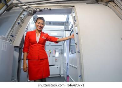 SINGAPORE - NOVEMBER 07, 2015: AirAsia crew member on board of Airbus A320. AirAsia is a Malaysian low-cost airline headquartered near Kuala Lumpur, Malaysia