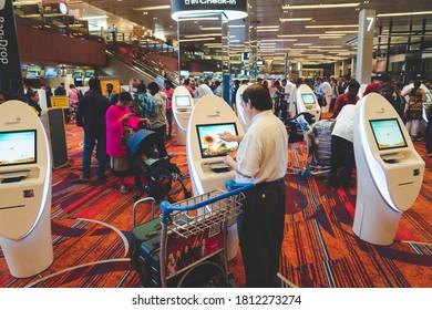 SINGAPORE - NOVEMBER 10, 2019 : A traveller at the self check-in kiosk at Terminal 3, Singapore Changi Airport. Changi Airport is a major civilian airport that serves Singapore