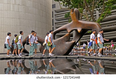 singapore, singapore - november 14, 2011: pupils visiting the bronze sculpture  large reclining figure of henry moore at ocbc centre on chulia street in central buisiness district near raffles place