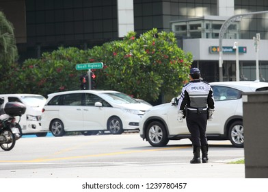 SINGAPORE - NOVEMBER 15, 2018: Unidentified police officer watch downtown traffic in Singapore.