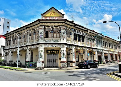 Singapore - November 19 2018: Row of vintage Peranakan shophouses with colourful shutters and exteriors against blue sky in historic Geylang