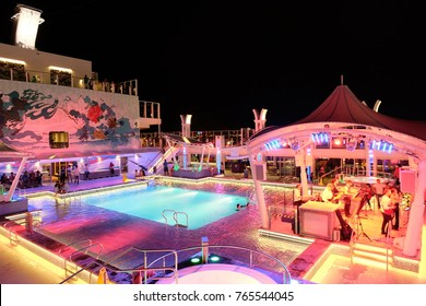 Singapore - November 25, 2017 : The Genting dream ship has giant swimming pool on the roof with the musicians and entertainers nearby the pool