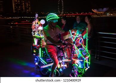 SINGAPORE, SINGAPORE - OCT 6, 2018: Man riding a LED light bicycle at Marina Bay.
