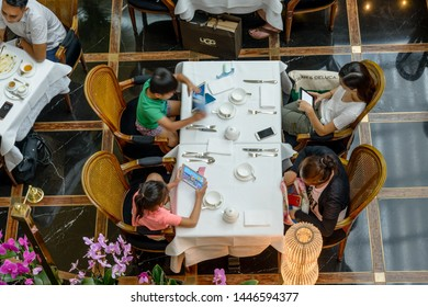 SINGAPORE, SINGAPORE - OCTOBER 07, 2016: A family group sitting at table with mobile devices in the Marina Bay complex.