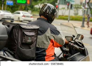 SINGAPORE - OCTOBER 07, 2016: An Uber Eats motor scooter delivery rider prepares to set off to deliver a food order to a client.