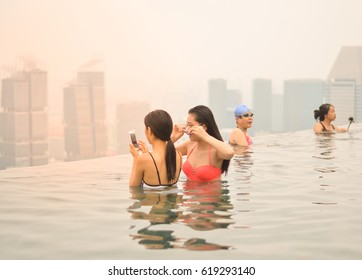 Singapore - October 18, 2015 : Unidentified Chinese asian girls use thier phone in Infinity pool view at Marina Bay Sands hotel in Singapore with building sunlight view scene background