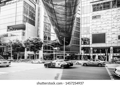 Singapore - October 21st 2015: Black and white image underneath the Orchard Gateway glass bridge on Orchard Road looking towards the entrance of the Orchard Central shopping mall with passing traffic