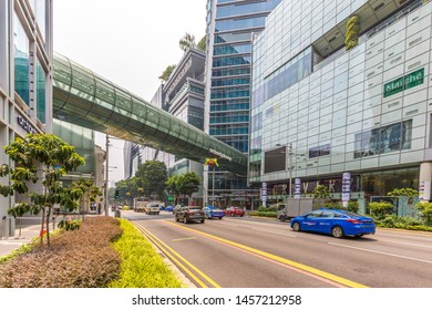 Singapore - October 21st 2015: Orchard Gateway glass bridge crossing over Orchard Road into Orchard Central shopping mall with taxis and traffic driving along the road in Singapore, Asia