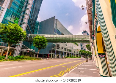 Singapore - October 21st 2015: Orchard Gateway glass bridge crossing over Orchard Road into Orchard Central shopping mall with a blue sky and clear roads in Singapore, Asia
