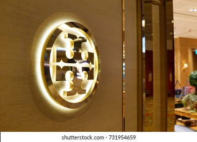 SINGAPORE - OCTOBER 4, 2017: Tory Burch Logo On Store Front Sign in Changi Airport. Tory Burch is an American fashion label owned, operated and founded by American designer Tory Burch.