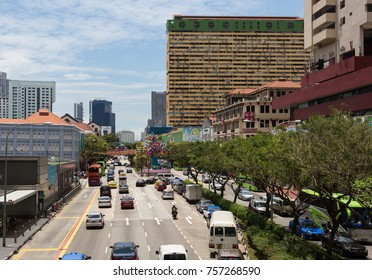 SINGAPORE - OCTOBER 6, 2017: Cars and other vehicles drive in a busy Chinatown street on a sunny day in Singapore. The city is a major business district in Asia