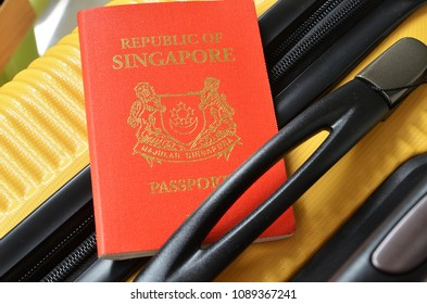 Singapore passport on a yellow suitcase. Travel concept