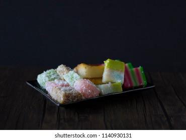 Singapore Peranakan Food Flat Lay. Peranakan Food on Wooden Table. Peranakan Kueh with Copy Space on Wooden Table. Asian Desserts. Nonya Kueh Lapis, Bingka Ubi, Kosui, Talam.