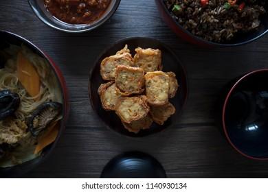 Singapore Peranakan Food Flat Lay. Peranakan Food on Wooden Table. Ngoh Hiang, Asian Fried Prawn Roll with Beancurd Skin, Chap Chye, Chili, Peranakan Fried Rice.