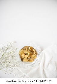 Singapore Salted Egg Chips Flatlay on White Table. Salted Egg Yolk Fish Skin. Asian snacks with tea and baby's breath flowers on white background.