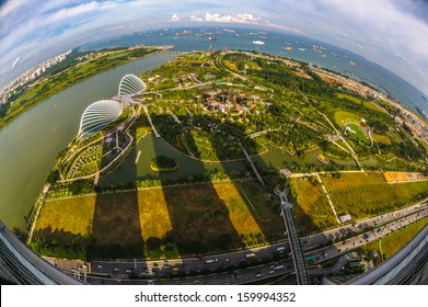 Singapore, Singapore - Sep 11 : Fisheye aerial View of the two domes of Gardens by the Bay park, Singapore with Marina Bay Sands towering shadows on September 11, 2013