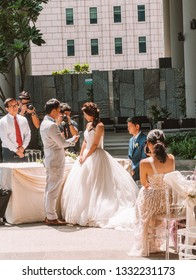 Singapore - Sept 2018: Bride and groom during Chinese wedding vow ceremony. Sweet asian flower girls wearing white dresses.  Bride in beautiful white wedding dress. Shy bride.
