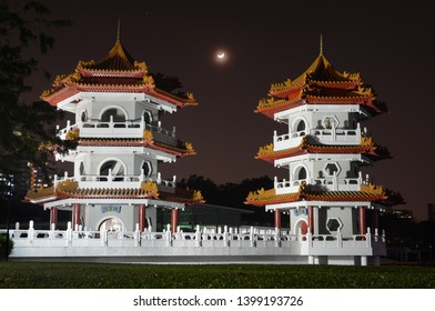 Singapore - September 13, 2018 - Crescent moon rising in night sky between the Twin Pagodas at the Chinese Garden in Singapore