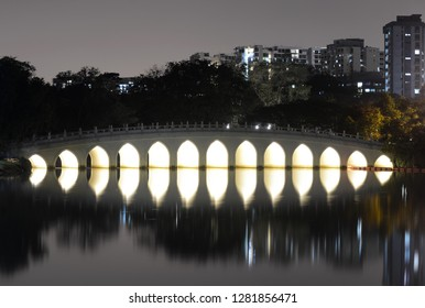 Singapore - September 13, 2018: White Rainbow Bridge reflection in water at night in the Chinese Garden, Singapore