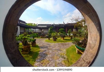 Singapore - September 14, 2018 - Moon gate in the Bansai Garden at Singapore's Chinese Garden