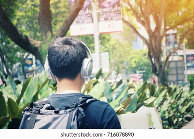 SINGAPORE - September 16, 2017: A man with headphones walking casually listening to music in downtown Singapore