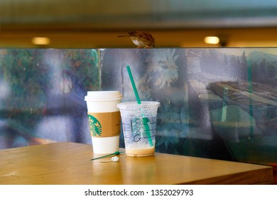 SINGAPORE - SEPTEMBER 2, 2018: Used Starbucks cups and a sparrow on the street of Asian metropolis. Illustrative editorial.