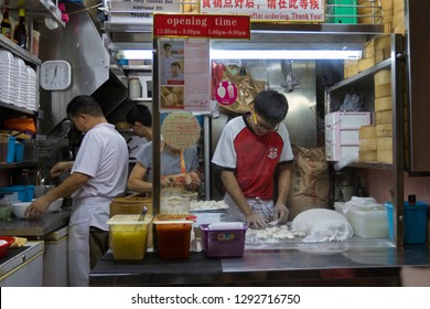 SINGAPORE - SEPTEMBER 2018: People at Zhong Guo La Mian Xiao Long Bao restaurant preparing noodles, dumplings at food stalls in Chinatown, Singapore on September 16, 2018. It received star in