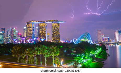 singapore ,september 2019; city scape of Marina bay tower with garden by the bay during the night time with thunderbolt .