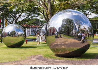 SINGAPORE - SEPTEMBER 30, 2017: Tourists taking photos of sphere sculpture installation in the front lawn of Asian Civilisations Museum in Singapore.