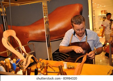 SINGAPORE - SEPTEMBER 4:  A rendezvous with Hermes craftmen, An unidentified artisan of the Hermes creates horse leather seat cover at Festival des Métiers at Paragon on September 4, 2011, Singapore.