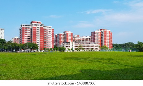 Singapore, SG - JANUARY 15, 2017: Scenery of The new modern red buildings that built near the wide green public park in Singapore local downtown in a blue sky day.