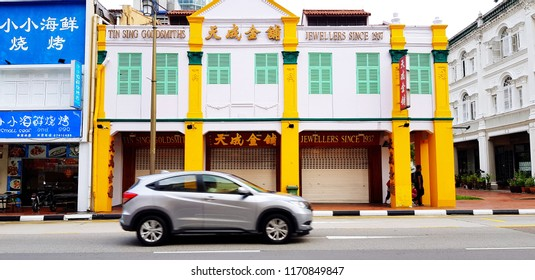 Singapore, Singapore-June 28, 2018: Blurred Gray car driving so fast on street with colorful(Yellow, Green, Brown and White) building in vintage or classic style background at Chinatown, Singapore