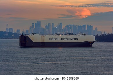 SINGAPORE STRAIT, SINGAPORE - Nov 14, 2017: Vehicles Carrier HOEGH TRAPPER passes by Strait of Singapore at sunset.
