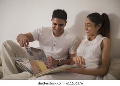 Singapore, Young man and woman looking at photo album