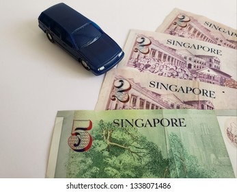 singaporean banknotes and figure of a car in dark blue