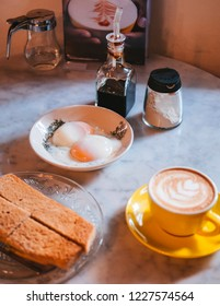 Singaporean breakfast with Kaya toast and soft-boiled eggs in vintage design plate and coffee Singaporean cuisine on marble table