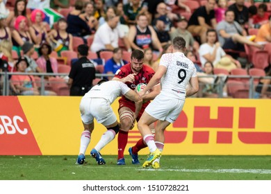 SINGAPORE-APRIL 13:England 7s team (white) plays against Wales 7s team (red) during Day 1 of HSBC World Rugby Singapore Sevens on April 13, 2019 at National Stadium in Singapore