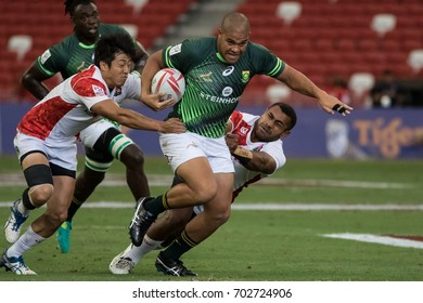 SINGAPORE-APRIL 15: South Africa 7s Team (green) plays against Japan 7s team (white/red) during Day 1 of HSBC World Rugby Singapore Sevens on April 15, 2017 at National Stadium in Singapore
