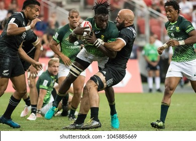 SINGAPORE-APRIL 16: South Africa 7s Team (green) plays against New Zealand 7s team (black) during Day 2 of HSBC World Rugby Singapore Sevens on April 16, 2017 at National Stadium in Singapore